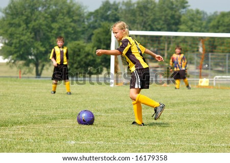 Young soccer girl prepares to kick ball during play - stock photo