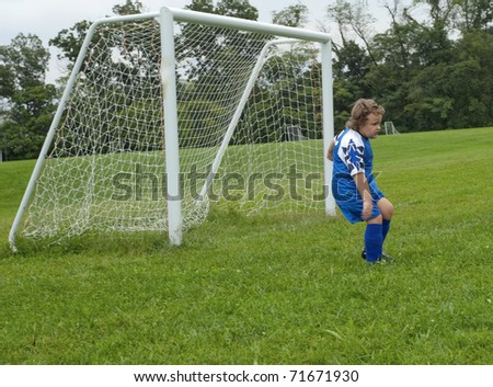 Young soccer goalie during game with net behind on green grass
