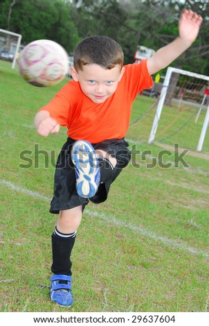 Young soccer player kicking ball in field
