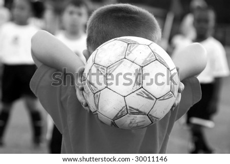 Young soccer player ready to throw in ball to defenders - stock photo