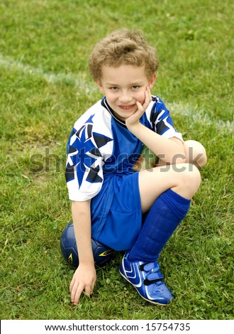 Young soccer player sitting on ball on sideline waiting turn - stock photo
