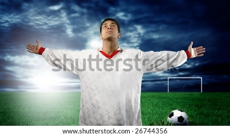 Young soccer player standing in a soccer field - stock photo