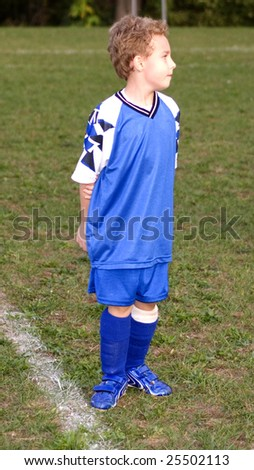 Young soccer player standing on soccer field waiting start of game - stock photo