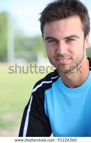 Young soccer player stood by pitch - stock photo