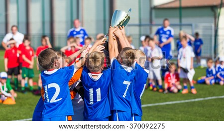 Young Soccer Players Holding Trophy. Boys Celebrating Soccer Football Championship. Winning team of sport tournament for kids children. Horizontal sport background. - stock photo
