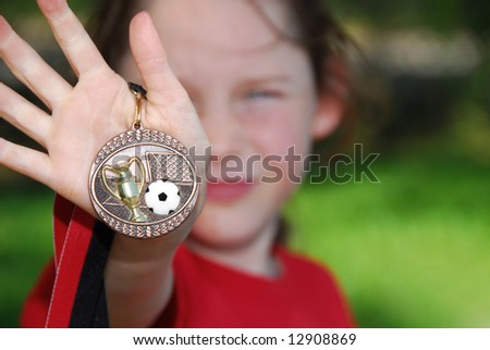 Young soccer playing girl showing off soccer medallion - stock photo