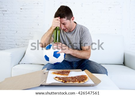 young soccer supporter man holding ball and beer bottle watching football game on television sitting at home couch looking dejected , sad and disappointed for failure or defeat  - stock photo
