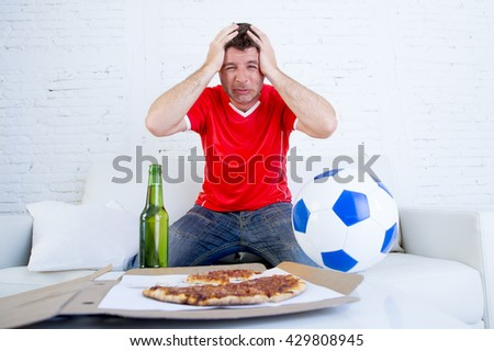 young soccer supporter man with beer bottle and ball watching football game on television at home couch dejected sad and disappointed for failure or defeat hands on his head - stock photo