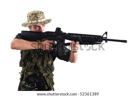 Young soldier aiming with M16 rifle