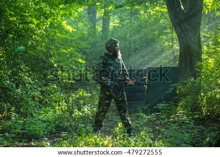 Young soldier bearded man in military camouflage and helmet with rifle in hands standing on post on background of green trees of forest and sun beams