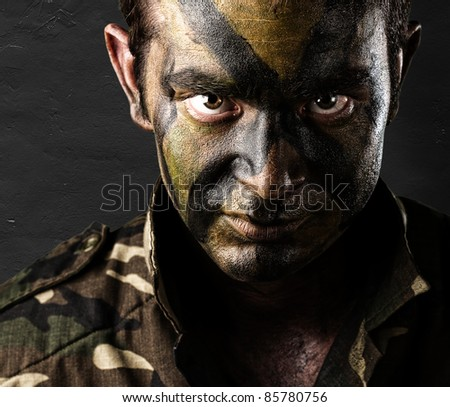young soldier face with jungle camouflage against a grunge wall - stock photo