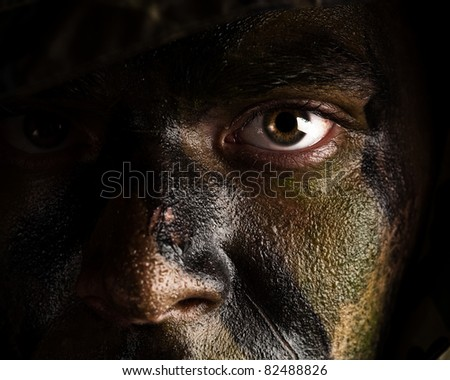 young soldier face with jungle camouflage paint - stock photo