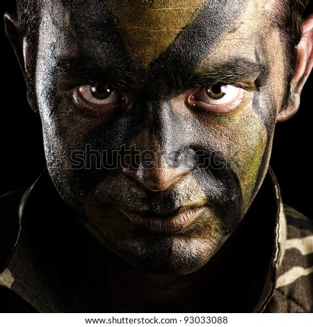 young soldier face with jungle camouflage paint on black background - stock photo