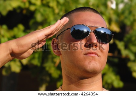Young soldier giving salute during basic training - stock photo