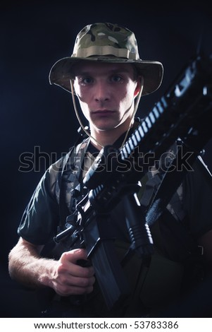 Young soldier holding M16 assault rifle.