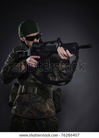 Young soldier in camouflage and ammunition with a gun. studio shot - stock photo