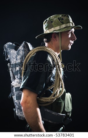 Young soldier in camouflage with backpack and rope.