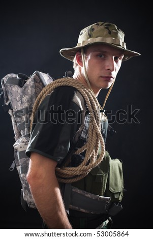 Young soldier in camouflage with backpack and rope ready for mission.