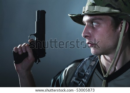 Young soldier in camouflage with gun.