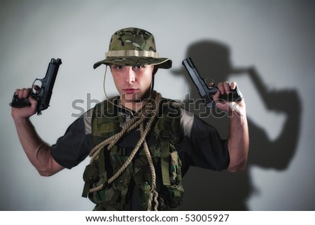 Young soldier in camouflage with guns.