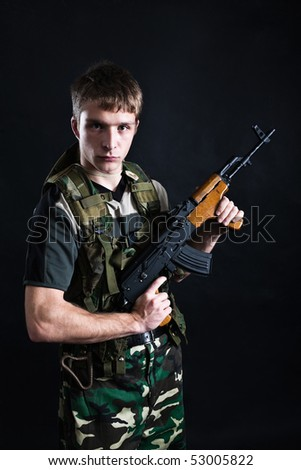 Young soldier in camouflage with Kalashnikov rifle.