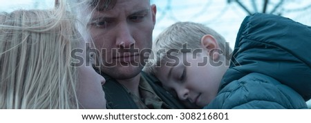 Young soldier is saying goodbye to his family - stock photo