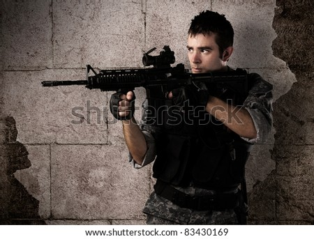 young soldier pointing a target against a grunge bricks wall