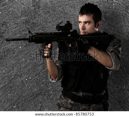 young soldier pointing a target against a grunge wall