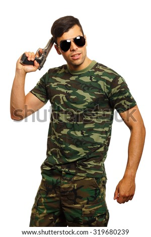 Young soldier posing with a gun to your head - stock photo