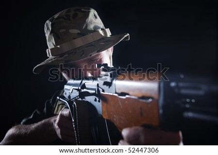 Young soldier with aiming Kalashnikov rifle.