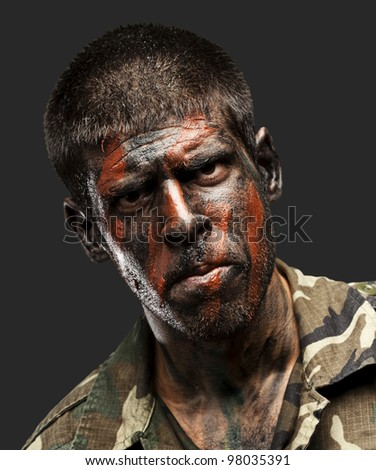 young soldier with camouflage paint looking very serious over black - stock photo
