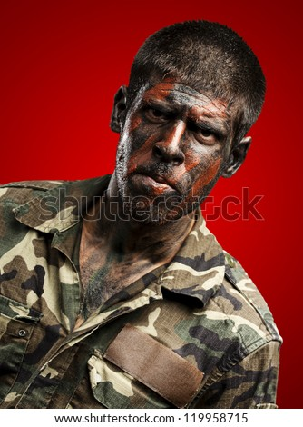 young soldier with camouflage paint looking very serious over red - stock photo