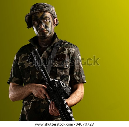 young soldier with jungle camouflage on a yellow background