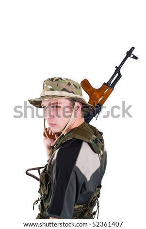 Young soldier with Kalashnikov rifle on shoulder.