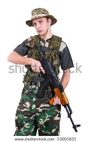 Young soldier with rifle against white background.