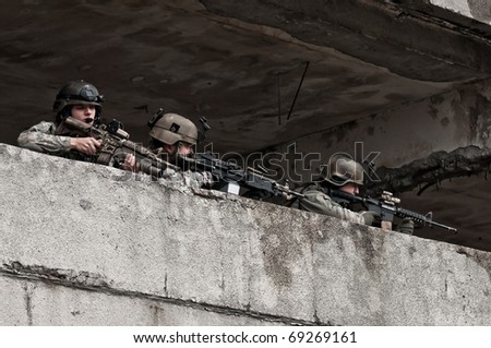 Young soldiers behind obstacle - stock photo