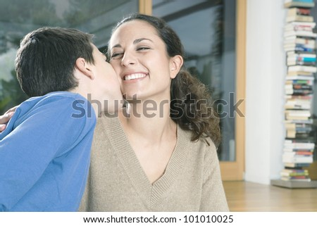 Young son kissing his mother on the cheek. - stock photo