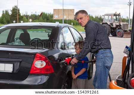 Young son looking at father refilling car at gas station  - stock photo