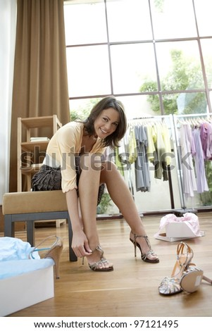 Young sophisticated woman trying on new shoes in a fashion store, smiling.