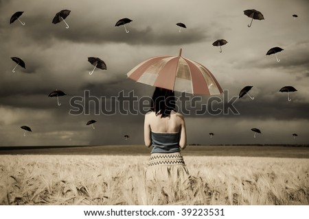 Young sorceress at wheat field with umbrella in rainy day.
