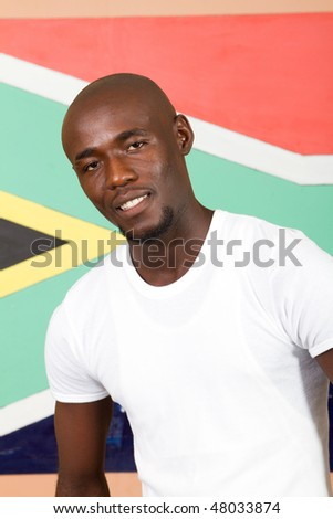 young South African man in front of South African flag smiling, 2010 FIFA world cup concept