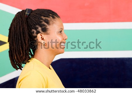 young South African woman in front of South African flag, 2010 FIFA world cup concept