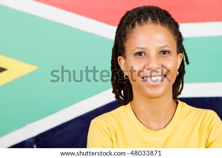 young South African woman in front of South African flag smiling, 2010 FIFA world cup concept