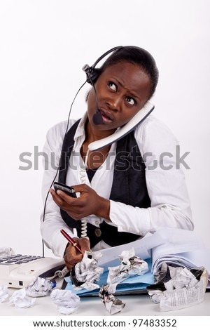 Young South African woman overwhelmed by work, telephones and stress. - stock photo