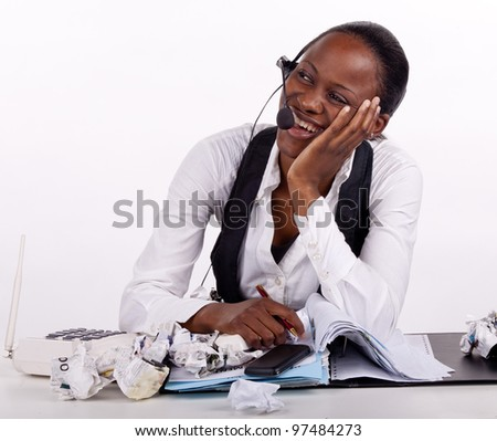 Young South African woman overwhelmed by work, telephones and stress, but smiling nonetheless. - stock photo