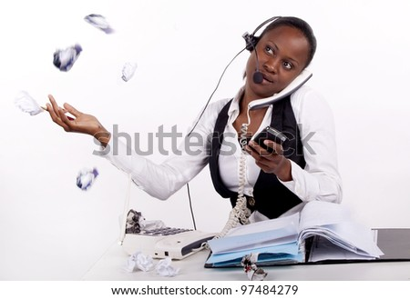 Young South African woman overwhelmed by work, telephones and stress, throwing paper in the air. Frustration! - stock photo