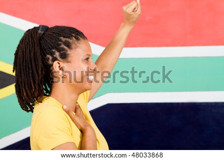 young South African woman salute in front of South African flag, 2010 FIFA world cup concept - stock photo