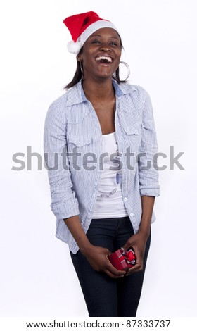 Young South African woman wearing a Santa hat and holding a present. - stock photo