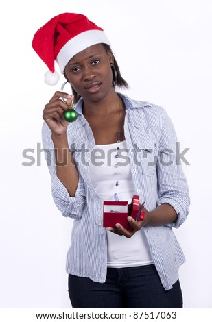 Young South African woman wearing a Santa hat and holding a present s he's displeased with. - stock photo