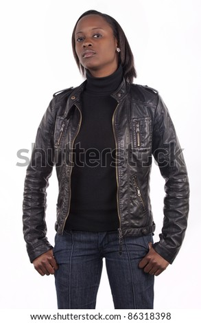 Young South African woman wearing black leather and a serious expression on a white background.